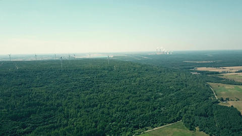 Aerial pan shot of distant smoking stacks of a traditional power plant and Footage
