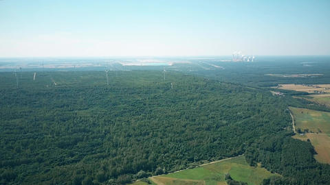 Aerial view of wind generators against smoking stacks of a traditional power Footage