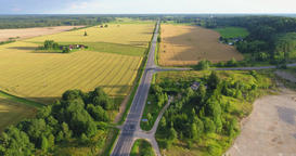 Aerial view of green countryside with cars and trucks driving through the fields Footage