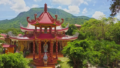 Drone Shows Ancient Pagoda Facade against Hills Blue Sky Live Action