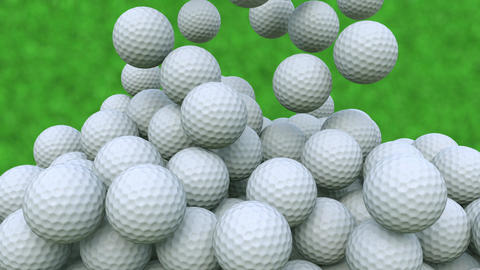 Multiple golf balls falling down against green grass background Footage