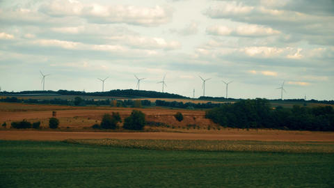 Distant spinning wind generators and field in Austria as seen from moving car Footage