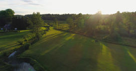 Aerial footage. Flying over the fields and forest at sunset with the sun's rays Footage