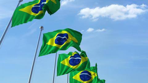 Row of waving flags of Brazil agaist blue sky, seamless loop Footage