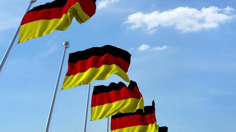 Row of waving flags of Germany agaist blue sky, seamless loop Footage