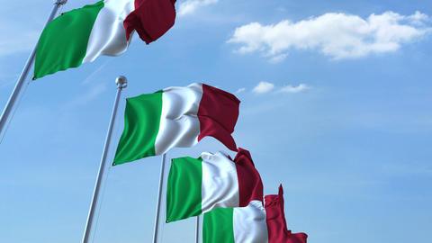 Row of waving flags of Italy agaist blue sky, seamless loop Footage