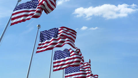 Row of waving flags of the United States agaist blue sky, seamless loop Footage
