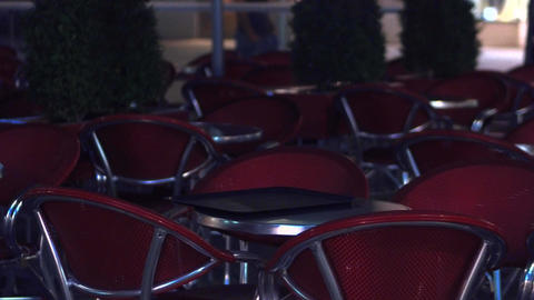 Empty tables and chairs of a street cafe at night Stock Video Footage
