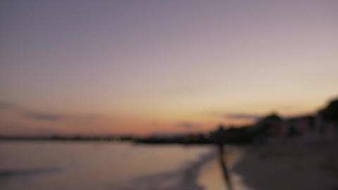 Silhouettes playing on the beach - out of focus sunset sea landscape Archivo