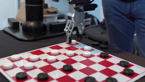 Robot playing checkers. Hand manipulator moves checkers. The robot makes a Footage