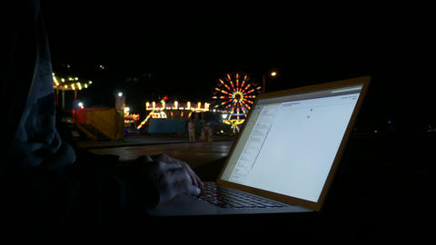 Checking emails on laptop computer outside at night Live Action