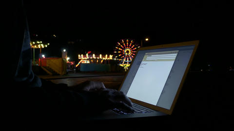 Typing late night emails from notebook pc at night with city lights in Footage