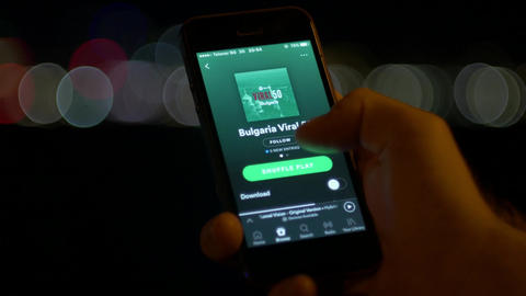 Playing songs on Spotify music searching application on smartphone at night Footage