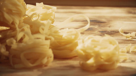 Uncooked tagliatelle, Italian pasta on a wooden table Footage