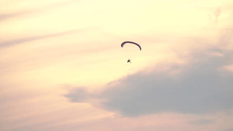 Unknown powered paraglider flying high in sunset sky Footage