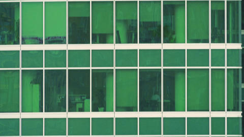 Vertical tilt telephoto shot of green tinted office skyscraper windows Footage