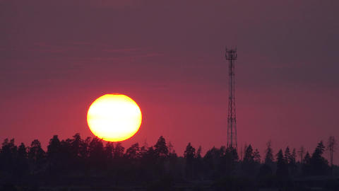 Time lapse of the sun setting behind cell tower Footage