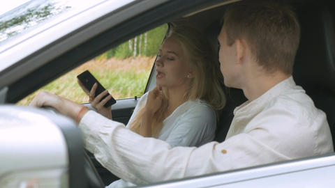 A blonde girl and her boyfriend are arguing, sitting in the car. Irritation and Footage