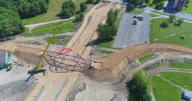 Construction site of bridge over road at summer day. Aerial view. Big crane Footage