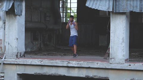 Male boxer doing shadow boxing exercise in an old abandoned factory Footage