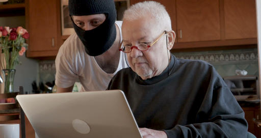 Hacker viewing an unsuspecting older man's private information on his computer Live Action