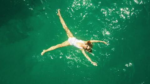 Aerial top down view of a beautiful young woman in a white swimsuit bathing in Foto