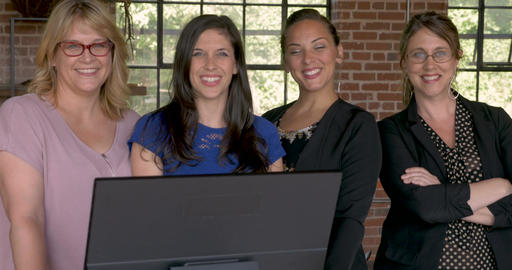 Portrait of four confident attractive successful business women smiling behind Footage