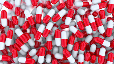 Falling red and white drug capsules or pills, shallow focus Footage