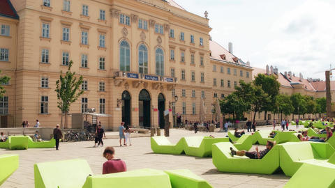 VIENNA, AUSTRIA - AUGUST 12, 2017. Young people relaxing on green benches at the Footage