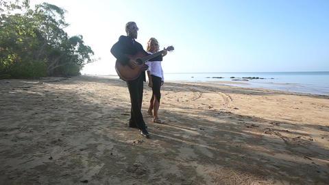 Blonde Guitarist Plays on Beach Blonde Girl Walks around at Dawn Footage