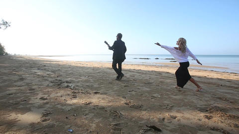 blonde girl chases leaving bearded guitarist on beach at sunrise Footage