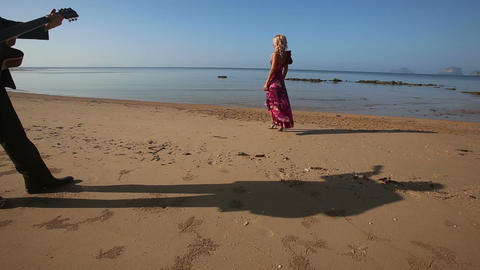 blonde sad girl in bright dress walks along beach Footage
