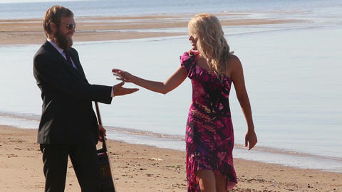 guitarist dances with blonde girl in red on beach Footage