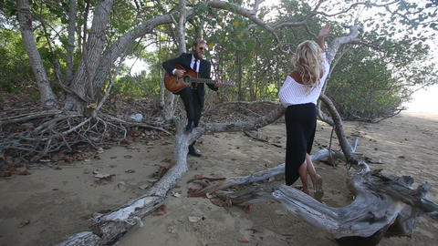 guitarist flirts with blonde girl she sits down on branch Footage