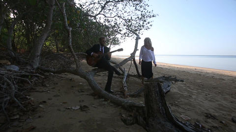 Guitarist Plays Sitting on Branch and Girl Sits by at Trees Footage