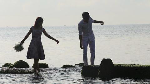 silhouette of guy helps girl walk on rocks in sea at dawn Footage