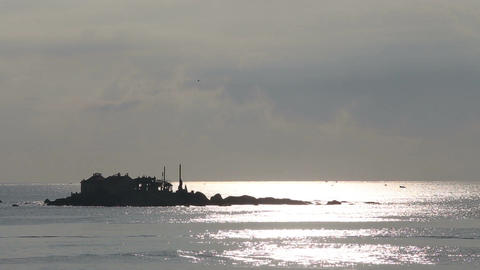 view of house on small cliff island in sea at dawn Footage