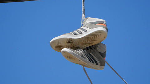Video of pair of shoes hang tossed telephone wire in 4K Filmmaterial