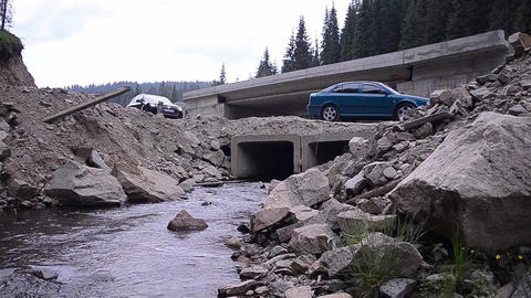 Auto traffic, the weather of rain, over a temporary bridge over a brook, while l Footage