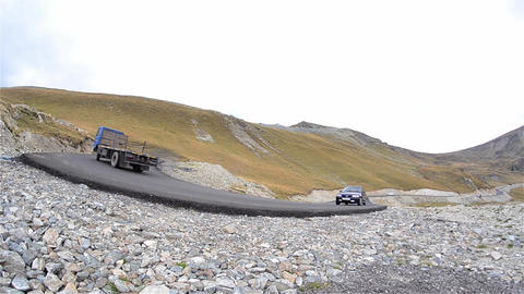 Column of cars running on paved mountain road that has many switchbacks and larg Footage