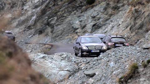 Column Of Cars Running On Paved Mountain Road That Has Many Switchbacks And Larg stock footage