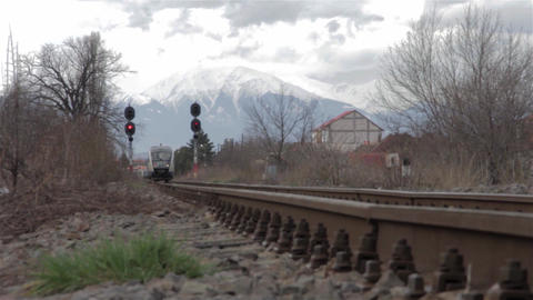 High speed train is approaching the station in a mountainous area where snowy pe Footage