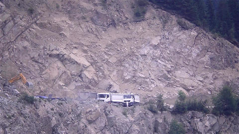 Industrial activity in a quarry where several trucks loaded by excavators expect Footage