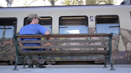 Man sitting on a bench in the station, look to the left and right of the people  Footage