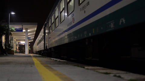 Night train entering a station and stops at the platform. Travellers him down wi Footage