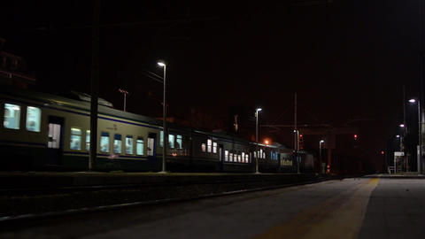 Night train entering a station and stops at the platform Travellers him down wit Footage