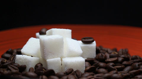 Coffee Beans and Sugar Cubes Close Up Rotating on a Red Plate Live Action