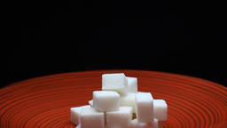 Sugar Cubes on a Red Plate Black Background Rotating Footage