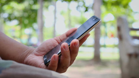 Close up shot hand of man using mobile smart phone in nature public park with Footage