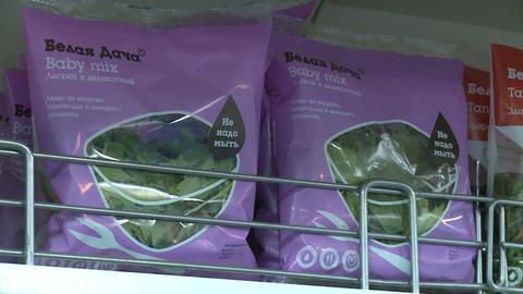 Closeup Camera Shows Belaya Dacha Salad Baby Mix in Packs Live Action